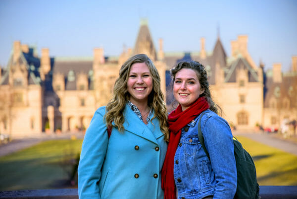 Women posing in front of the Biltmore at Christmas