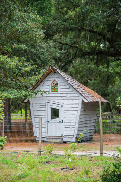 Grey building with stained glass rooster window at Daufuskie Island Community Farm
