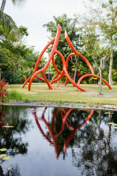 Large orange modern sculpture with reflection in water at Naples Botanical Gardens
