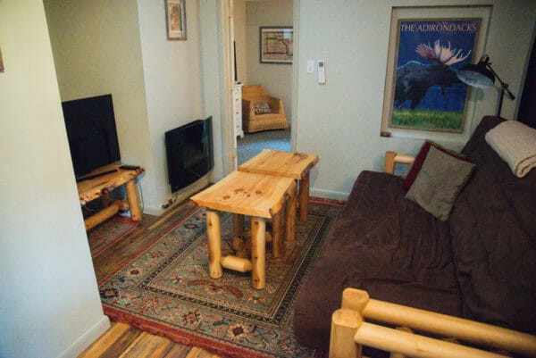 Interior of Airbnb in Plattsburgh, NY with brown couch and light wooden coffee tables