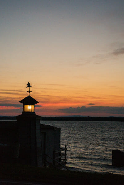 View of Lake Champlain at sunset with boat house light