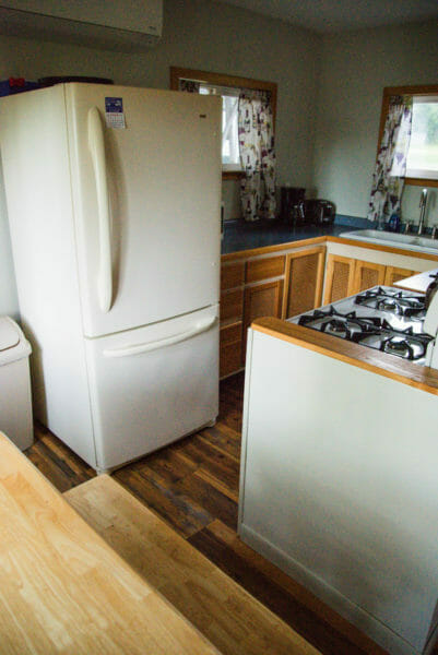 Interior of Airbnb in Plattsburgh, NY of kitchen with white fridge and wooden cabinets