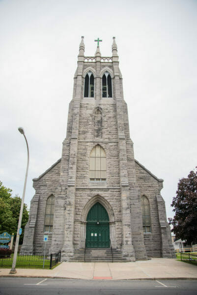 Grey stone church with green doors in Plattsburgh, NY