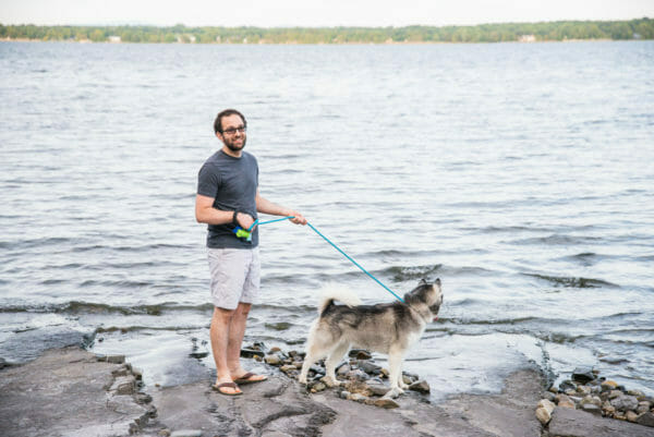 Man and Siberian Husky next to lake