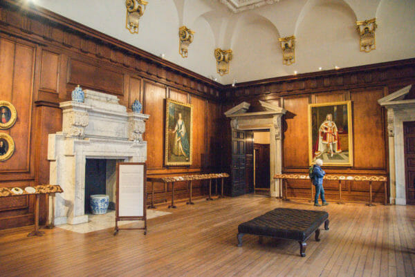 Hall in Hampton Court with paintings of kings on the walls