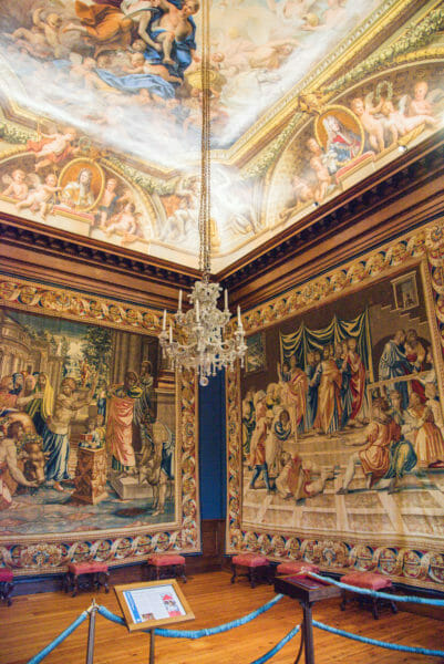 Large tapestries and a painted ceiling in a room in Hampton Court