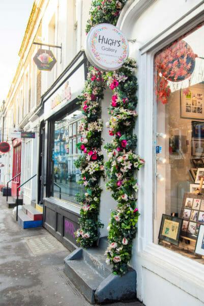 Hugh's Gallery with flower archway around door in Notting Hill