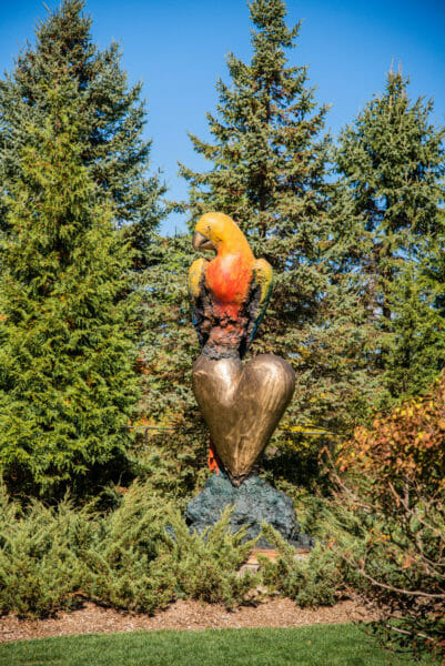 Large parrot on a heart statue at Meijer Gardens